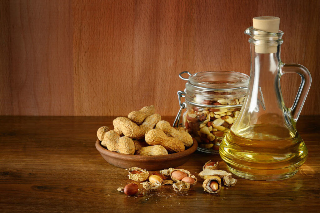 Bowl of peanuts and bottle of peanut oil