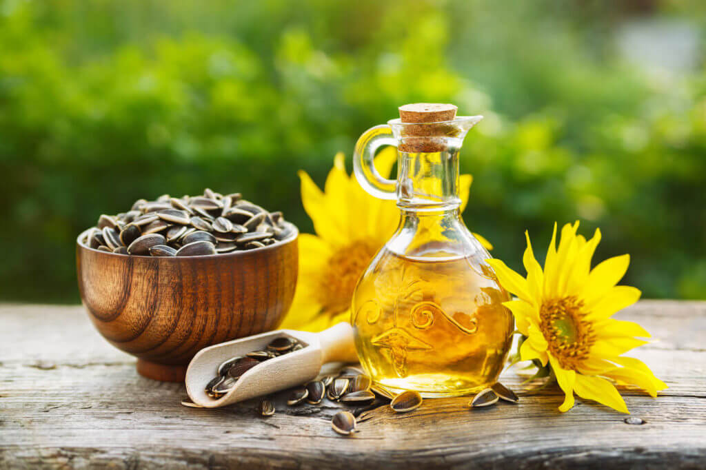 Organic sunflower oil in a small glass jar with sunflower seeds and fresh flowers