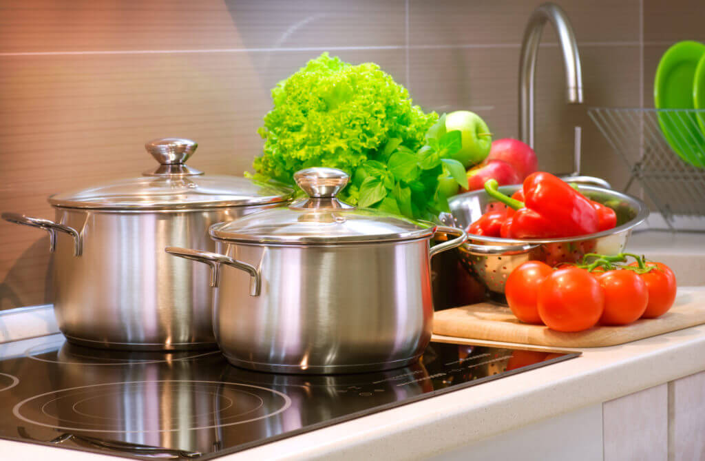 Metal pots, tomatoes, peppers and green vegetables on a stove