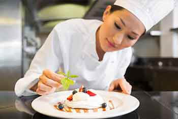 A student adds garnish to a pastry assignment