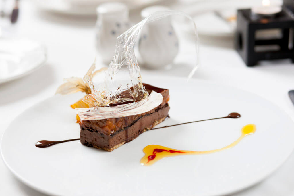 Chocolate dessert on white plate with clear transparent decoration