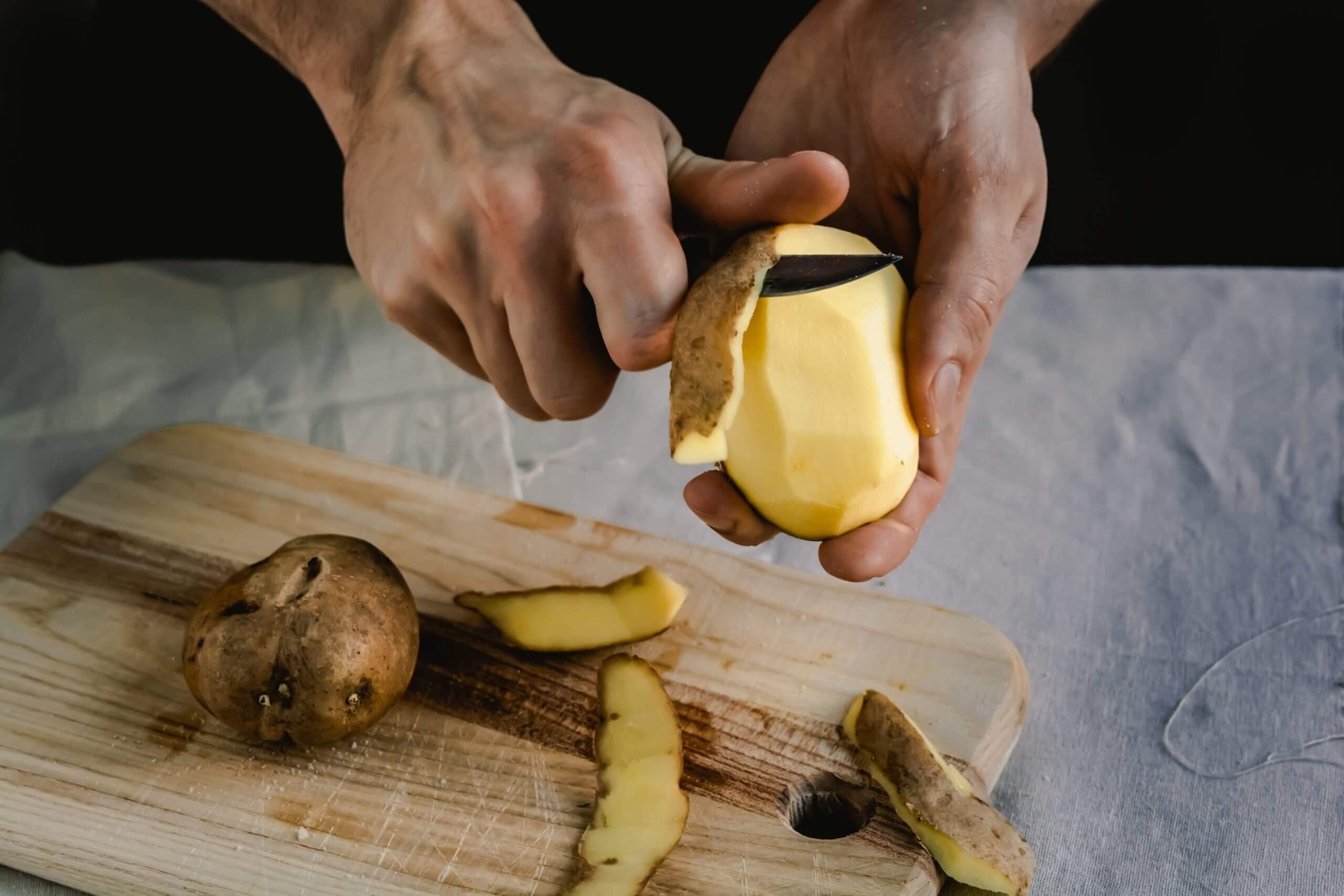Chef peeling potatoes on wooden cutting board