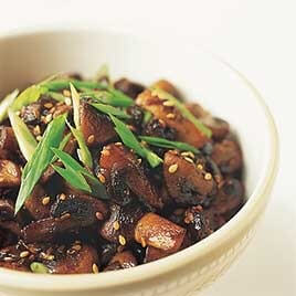 Bowl of sauteed mushrooms with sesame seeds and green onion